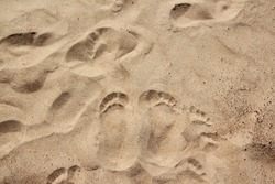 Footprint or trace in summer sand beach or coastline on holidays - background texture - top view