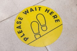 footprint sign for stand in shopping mall, supermarket. Social distancing with COVID-19 coronavirus crisis. yellow footprint sign with text caution social distance
