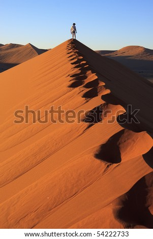 Footprints and man looking at the view at the top of a dune