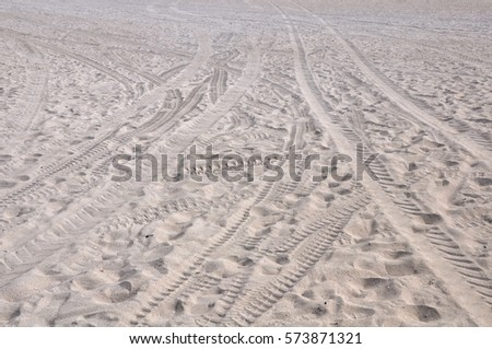 Footprints and tracks in the sand on the beach