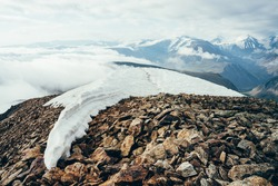 Footprints in snow on mountain top above thick clouds with view to giant mountains and glaciers. Snow on mountain peak among thick low clouds. Atmospheric alpine landscape. Wonderful highland scenery.