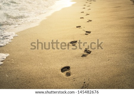 Footprints in the sand at sunset. Beautiful sandy tropical beach with sea waves. Footsteps on the shore.