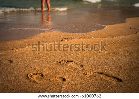 Footprints in the sand. Defocused legs in the background.