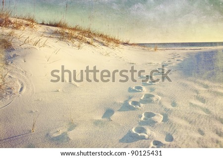 Footprints in the sand dunes leading to the ocean at sunset. Soft artistic treatment with canvas texture, grain and brush strokes added for effect. #90125431