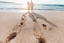 Footprints in the sand from a man and a girl at sunset