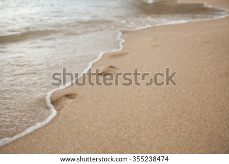 footprints in the sand on a beach washes off a wave. blurs. background. #355238474