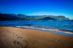 Footprints in the sand on the beach in Kauai, Hawaii in the Hanalei Bay.