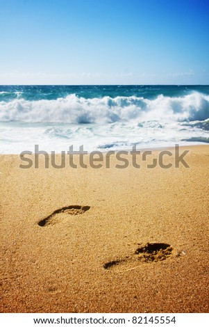 footprints in the sand with blue ocean and waves