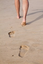 Footprints in wet sand in a line with a man walking on the beach