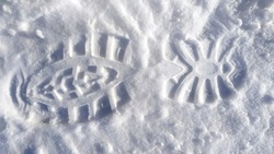 Footprints of a man's boot in the snow. A clear imprint of the pattern of the sole of the boots on a snowy field.