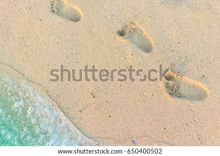 Footprints of baby on the sand beach with a wave of blue tropical sea in sunny day. Kids summer holidays activity concept. Copy space. Top view.