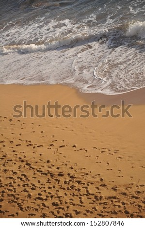 Footprints on a sandy beach near the waves in Lahaina, Maui, Hawaii