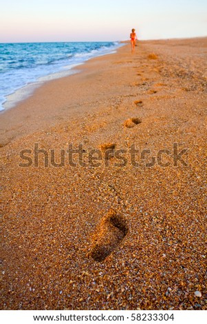 Footprints on beach in evening