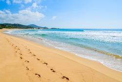 Footprints on beautiful sandy Chia beach and turquoise sea water, Sardinia island, Italy