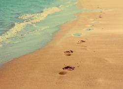 footprints on sand beach along the edge of sea - vintage retro style