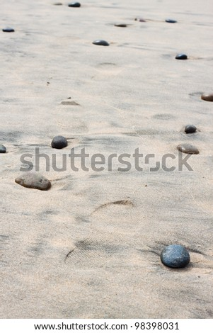 footprints on sand with many stones