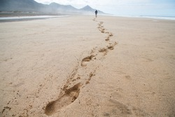 Footprints on sandy beach. Lonely man go along the beach leaving footprints on sand