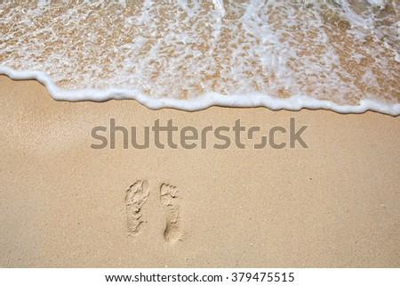 Footprints on sea shore. Sea water wave. Beach Vacation  #379475515