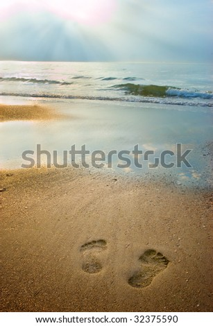 Footprints on the beach at sunset with soft light