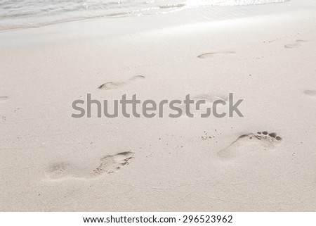 Footprints on the beach. Footsteps of people walking on the beach by the sea.