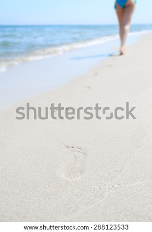 Footprints on the beach. Lonely woman departing into the distance over the sea. Small depth of field
