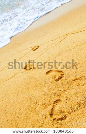 Footprints on the beach near the surf wave