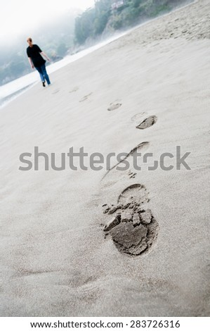 footprints on the beach sand on cloudy day and young woman walking on background