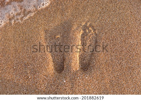 Footprints on the beach sand.Traces on the beach. Footsteps