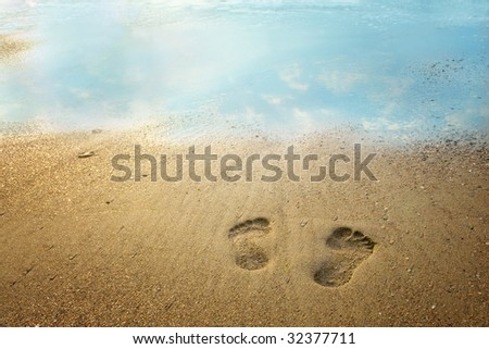 Footprints on the beach with the sky reflected in the water