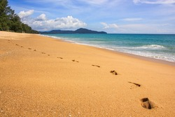 Footprints on the sand along endless pristine empty beach on scenic ocean landscape background. Wide well-conditioned sandy beach with imprints of footsteps on tropical idyllic island.