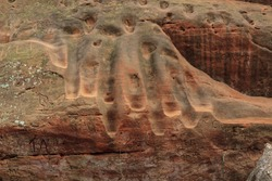Footsteps and graffiti worn into soft sandstone canyon walls in Oklahoma's Red Rock Canyon State Park