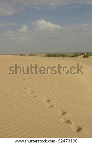 stock-photo-footsteps-in-sahara-desert-and-blue-sky-with-some-clouds-in-background-52473190.jpg