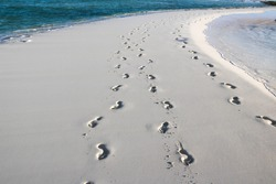 Footsteps in the sand with blue ocean water and waves on both sides