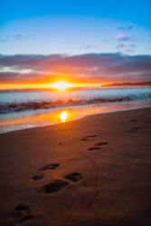 Footsteps on Beach at Sunset