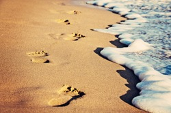 Footsteps on the beach by the sea in summer