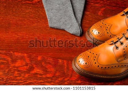 Footwear Compositions Made Up of Mens Fashionable Tanned Brogues Boots and Pair of Socks Placed Together. Over Wooden Background.Horizontal Image #1101153815