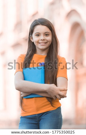 For creative learning. Happy schoolgirl outdoors. Little schoolgirl back to school. Small schoolgirl hold book. Fashion look of cute schoolgirl. Casual style. School and education. School library.
