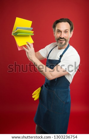 For dusting surfaces. Mature man holding cleaning cloths of assorted colors. Eldery housekeeper presenting cleaning towels. Senior man in apron with rubber gloves. Household worker. Household service. #1303236754