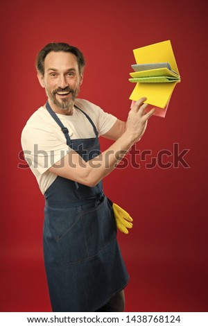 For dusting surfaces. Mature man holding cleaning cloths of assorted colors. Eldery housekeeper presenting cleaning towels. Senior man in apron with rubber gloves. Household worker. Household service. #1438768124