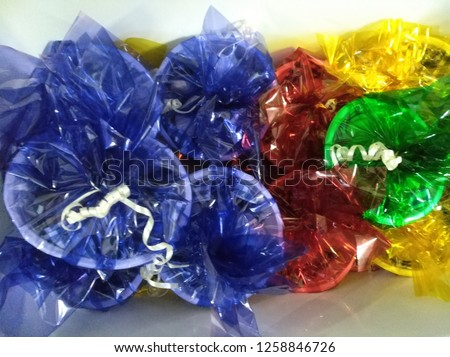for purim Mishloach manot wrapped in colored paper Delivery of candy wrapped in colored paper Bowls Packed with cellophane in a transparent blue, transparent green and yellow  #1258846726