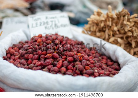 For sale at a famers market, dried red rosehips (rosa canina), a fruit from the blossoms of wild rose plants known for its medicinal properties. Also called rose haw,  rose hep and hop fruit.  Stock photo ©