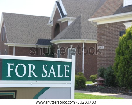 for sale sign in front of a new house - stock photo