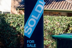 For sale sign near the residential building house with 'SOLD' sold sticker on it. Auction clearance rate