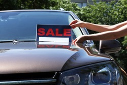 For sale sign on windshield of car.