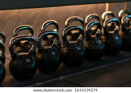 For you to choose. Stylish kettlebells weights made of black leather and iron lying in a row on the shelf in workout gym. Sport, lifting, healthy lifestyle concept. Horizontal shot.