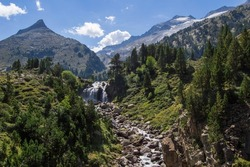 Forau d'Aigualluts waterfall with mountains and Aneto snowy peak in the background, in Benasque, Huesca, Spain. Alpine landscape in Posets Maladeta natural park, Spanish Pyrenees