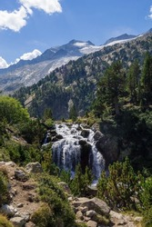 Forau d'Aigualluts waterfall with mountains and Aneto snowy peak in the background, in Benasque, Huesca, Aragon, Spain. Alpine landscape in Posets Maladeta natural park, Spanish Pyrenees