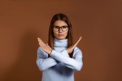 Forbidden. Pretty caucasian woman with dark hair wearing glasses and light blue sweater makes denial hand gesture, keeps arms crossed over chest, demonstrates stop sign, isolated on brown background