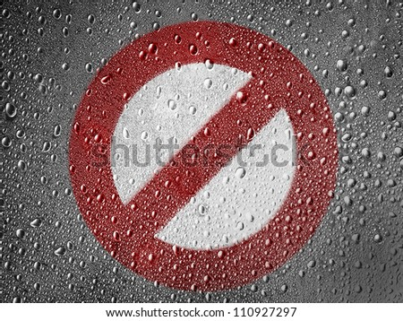 Forbidden sign painted on metal surface covered with rain drops