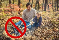 forbidden to make a fire. father and excited son sitting in tent in forest camping with bonfire